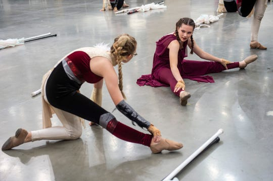 Mater Dei sophomore Jessie Bacon, right, stretches with the rest of the color guard before performing at the ISSMA State Marching Band Finals at Lucas Oil Stadium in Indianapolis, Ind., Saturday, Nov. 9, 2019. Mater Dei placed tenth in the Class D competition.