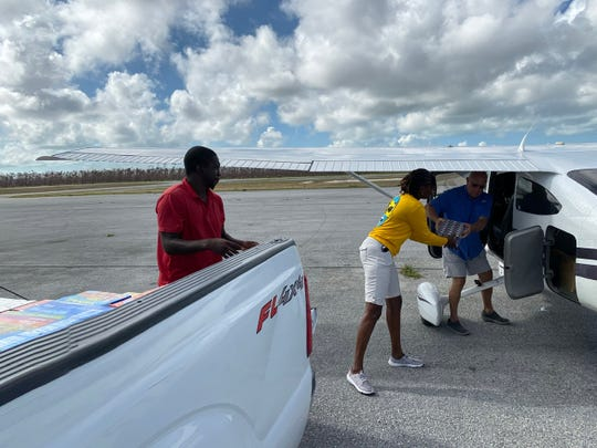 Tanique Pratt-Brutus, in yellow shirt, a Bahamian contact for the Sundowner Flying Club of Fort Myers,  helps load supplies the club brought recently.