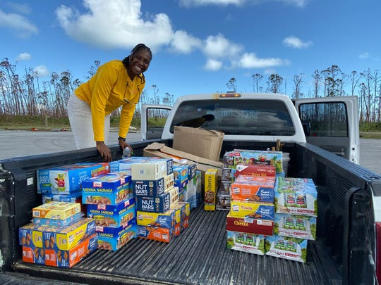 Tanique Pratt-Brutus, a Bahamian contact for the Sundowner Flying Club of Fort Myers,  helps load supplies the club brought recently.