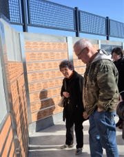 Dolly Schenkoski of Gillett and her friend, Gary Brainard of Green Bay, look over one section of the new Oconto Falls Veterans Monument, following its dedication on Saturday, Nov. 9. Her late husband Walter served in the Army.