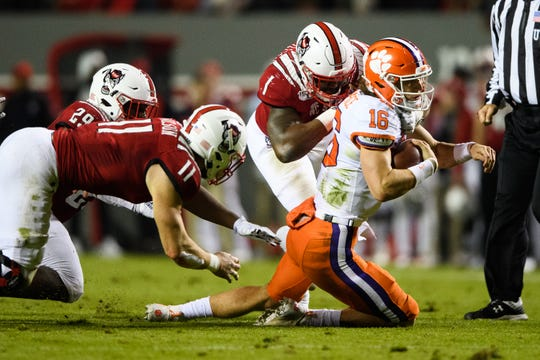 Clemson quarterback Trevor Lawrence (16) is taken down by NC State defensive end James Smith-Williams (1) and linebacker Payton Wilson (11) during their game at Carter-Finley Stadium Saturday, Nov. 9, 2019.