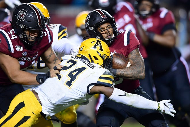 Akeem Davis-Gaither (24) of the Appalachian State Mountaineers tackles Rico Dowdle (5) of the South Carolina Gamecocks during their game at Williams-Brice Stadium.