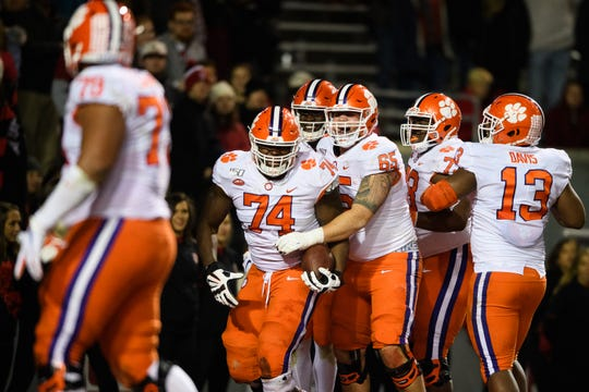 Clemson offensive guard John Simpson (74) celebrates with his teammates after scoring a touchdown during their game against NC State at Carter-Finley Stadium Saturday, Nov. 9, 2019.