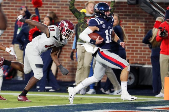 Ole Mis quarterback John Rhys Plumlee (10) outruns New Mexico State defensive back Austin Perkins (19) on his way to a 18-yard touchdown in a college football game in Oxford, Mississippi on Saturday, Nov. 9.