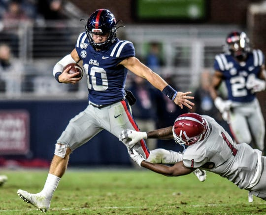 Ole Miss quarterback John Rhys Plumlee (10) avoids an attempted tackle by New Mexico State defensive back Ray Buford Jr. (1) during an NCAA college football game in Oxford, Miss., Saturday, Nov. 9, 2019.