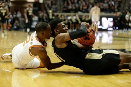 Purdue forward Aaron Wheeler (1) and Texas guard Matt Coleman III (2) dive for a loose ball during the first half of an NCAA Men's basketball game, Saturday, Nov. 9, 2019 at Mackey Arena in West Lafayette.