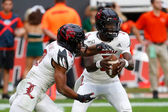 Louisville quarterback Micale Cunningham fakes a handoff to running back Javian Hawkins, left, during the first half of an NCAA college football game, Saturday, Nov. 9, 2019, in Miami Gardens, Fla.