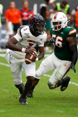 Miami linebacker Michael Pinckney (56) rushes Louisville quarterback Micale Cunningham (3) during the first half of an NCAA college football game, Saturday, Nov. 9, 2019, in Miami Gardens, Fla.
