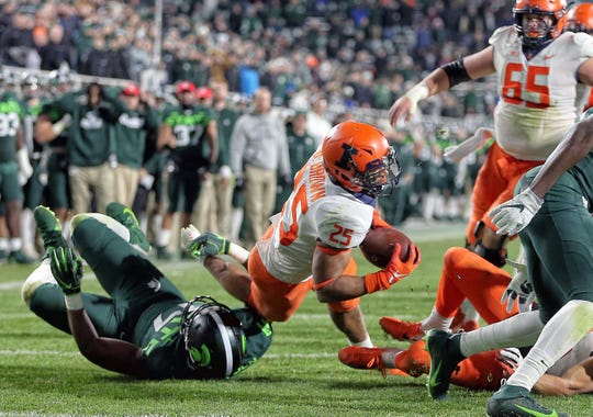 Nov 9, 2019; East Lansing, MI, USA; Illinois Fighting Illini running back Dre Brown (25) is tripped up by Michigan State Spartans linebacker Tyriq Thompson (17) during the second half of a game at Spartan Stadium. Mandatory Credit: Mike Carter-USA TODAY Sports