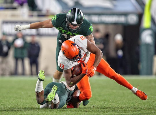 Nov 9, 2019; East Lansing, MI, USA; Illinois Fighting Illini wide receiver Caleb Reams (13) is tackled by Michigan State Spartans linebacker Noah Harvey (45) and Michigan State Spartans cornerback Shakur Brown (29) during the second half of a game at Spartan Stadium. Mandatory Credit: Mike Carter-USA TODAY Sports