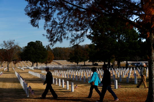 Visitors tend to the graves of fallen military service members after a Veterans Day Ceremony at the West Tennessee State Veterans Cemetery on Sunday, Nov. 10, 2019.