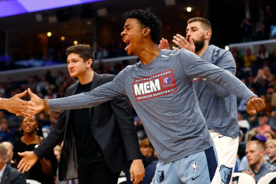 Grizzlies guard Ja Morant cheers his teammates on from the bench during Saturday's game against the Mavericks.
