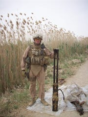 Erik Smith served two deployments in Iraq with Milwaukee-based Marine Reserves Fox Co., 2nd Battalion, 24th Marines. He poses with weapons caches discovered on a patrol in Anbar Province in 2008.