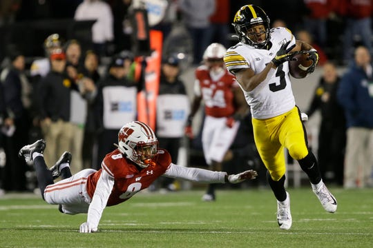 Iowa Hawkeyes wide receiver Tyrone Tracy, Jr. evades the diving tackle of Badgers cornerback Deron Harrell on a 75-yard touchdown reception in the fourth quarter.