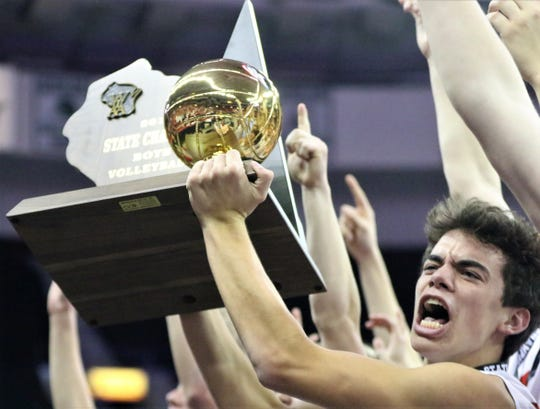 Kimberly's Tony Wisneski hoists the state championship trophy after defeating Germantown in the WIAA state boys volleyball final on Nov. 9, 2019 at the Resch Center.