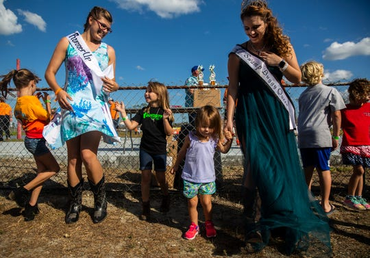 Swamp Buggy Queen Courtney Mee, third right, and the runner up Hope Gray, second left, dance with children during the Swamp Buggy Races at Florida Sports Park on Sunday, November 10, 2019, in Naples.