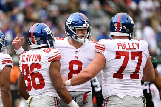New York Giants quarterback Daniel Jones (8) celebrates Darius Slayton's (86) touchdown with center Spencer Pulley (77) in the first half. The New York Jets host the New York Giants in an NFL game on Sunday, Nov. 10, 2019, in East Rutherford.