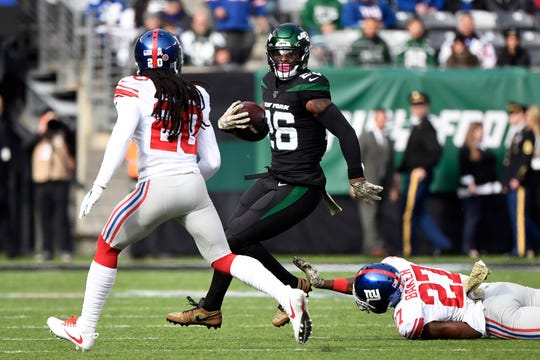 New York Jets running back Le'Veon Bell (26) breaks a tackle by New York Giants cornerback Deandre Baker (27) in the first quarter during an NFL game on Sunday, Nov. 10, 2019, in East Rutherford.