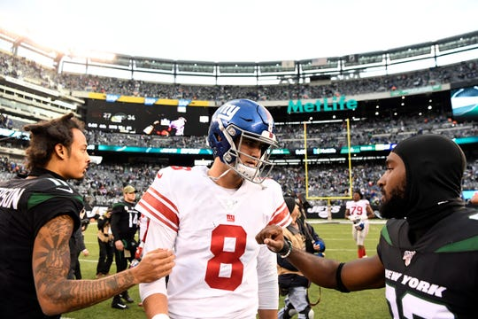 New York Jets wide receivers Robby Anderson, left, and Jamison Crowder, right, greet New York Giants quarterback Daniel Jones (8) after the game. The New York Jets defeat the New York Giants, 34-17, on Sunday, Nov. 10, 2019, in East Rutherford.