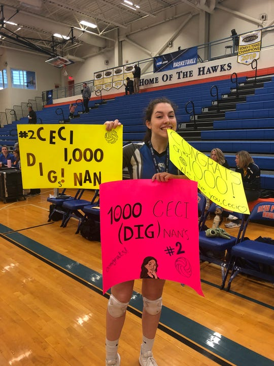 Millbrook's Cecilia Dignan poses with posters made to commemorate the senior recording her 1,000th career dig on Sunday.
