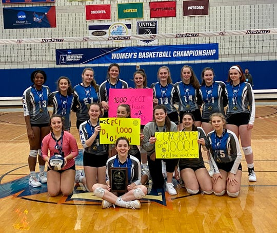 The Millbrook volleyball team poses with posters commemorating senior Cecilia Dignan reaching 1,000 digs in their victory over Burke Catholic to win the Section 9 Class C title on Sunday.