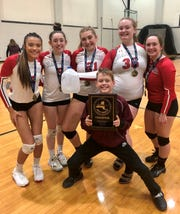 Coach Stacie Totman's son, Patrick, holds the Section 9 championship plaque as he poses with Red Hook volleyball players. From left: Ashley Vosburgh, Mackenzie Wade, Sadie Kubsch, Emily Feller and Anna Marcotte.