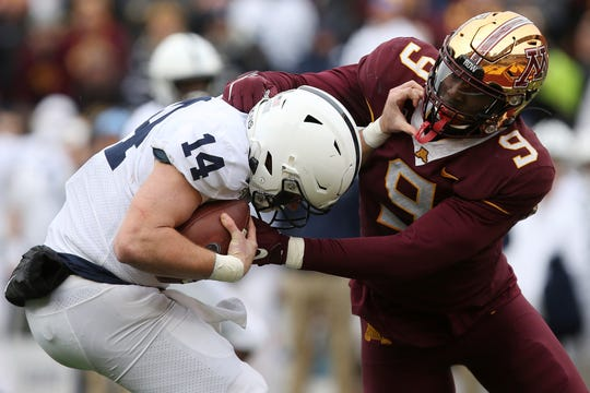 Minnesota defensive lineman Esezi Otomewo (9) grabs Penn State quarterback Sean Clifford (14) during an NCAA college football game Saturday, Nov. 9, 2019, in Minneapolis. Minnesota won 31-26. (AP Photo/Stacy Bengs)