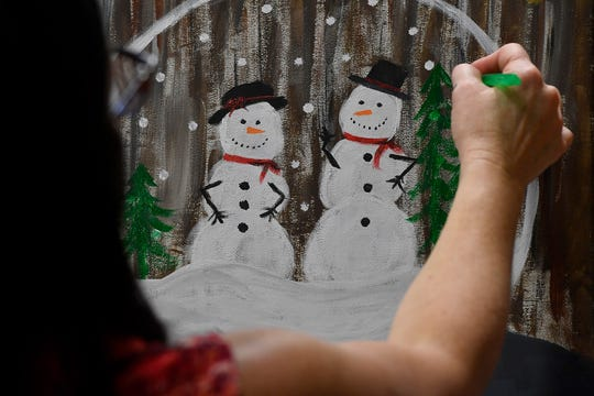Kimber Sutton of York putts the finishing touches on her snow globe painting, at Leg Up Farmers Market, Sunday, November 10, 2019.John A. Pavoncello photo
