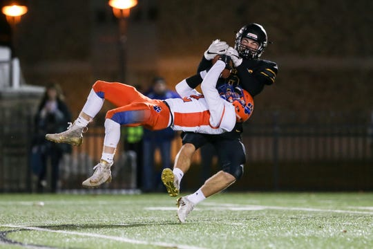 Alexander Minnehan (2) of Livonia intercepts a pass in front of HFL's Cary VanNewkirk (8) during the Section V Class B football championship.