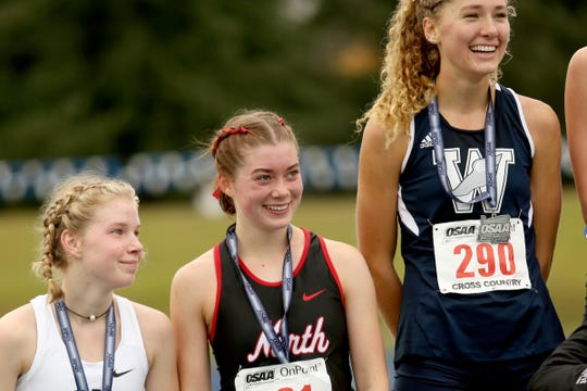 North Salem's Abi Swain is awarded a fourth place medal  following the OSAA Class 5A girls cross country state championship at Lane Community College in Eugene on Nov. 9, 2019. Swain and North Salem each placed fourth.