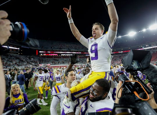 LSU Tigers quarterback Joe Burrow (9) celebrates as teammates hoist him after they defeated the Alabama Crimson Tide 46-41 during the second half of an NCAA college football game at Bryant-Denny Stadium.