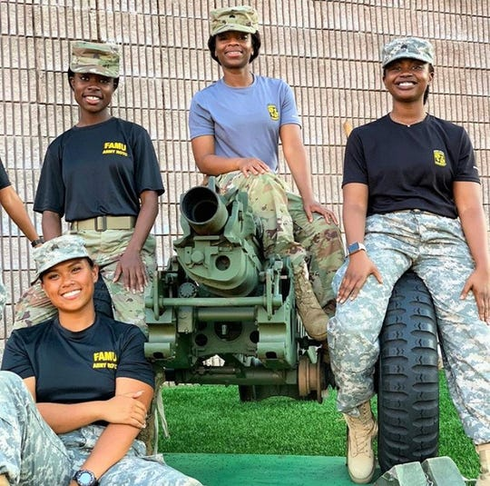 Rattler Battalion cadets Alelee Figueroa (bottom left), Jasniqua Williams (top left), Crystal Hill and Robbi Wilson (right) work firing the cannon during a football game at Bragg Memorial Stadium.