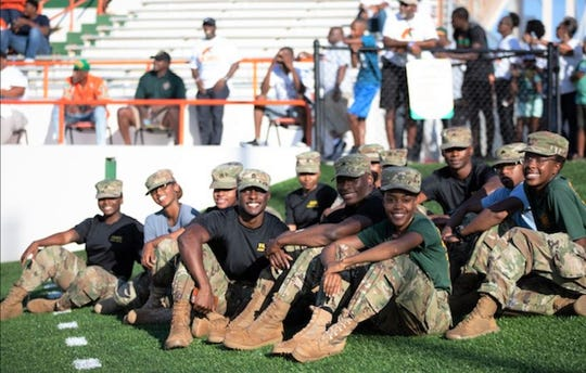 Cadets from the Rattler Battalion ROTC hang out near the south end zone at Bragg Memorial Stadium.