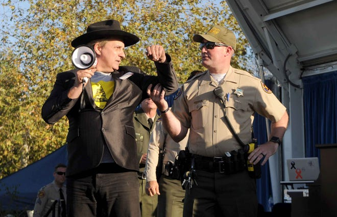 Bruce Boyer is arrested after getting up on stage shortly before the Thursday's dedication of the permanent Borderline memorial at Conejo Creek Park North in Thousand Oaks.
