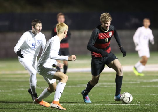 Rye's Alex Vollbrecht (9) works the ball against the Goshen defense in the NYSPHSAA class A boys soccer regional finals at Pace University in Pleasantville on Saturday, November 9, 2019.