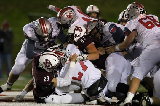 John Glenn's Ben Judd (23) and Blaize Baker stop St. Clairsville running back Aaron Jordan during the Muskies week 11 win over the Red Devils.