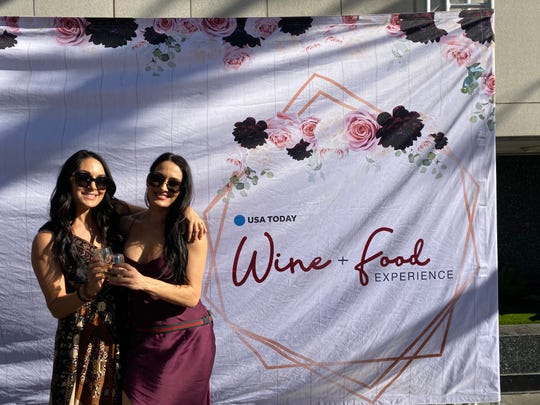 Wrestling-duo-turned-wine-aficionados Brie, left, and Nikki Bella pose together at the USA TODAY Wine and Food Experience after their meet-and-greet.