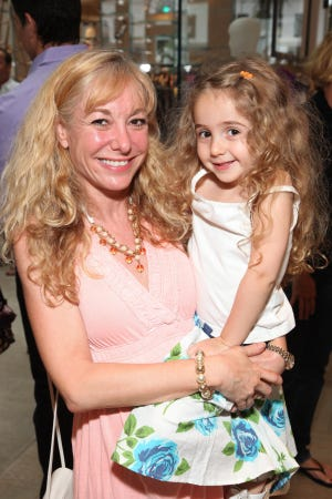 Laurel Griggs, then 4, in the arms of her mom Liz Griggs at the Elie Tahari & CFDA Sparkle in the Sun event on July 10, 2010, in New York.