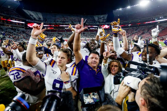 LSU quarterback Joe Burrow (9) and coach Ed Orgeron celebrates with teammates after defeating the Alabama at Bryant-Denny Stadium.
