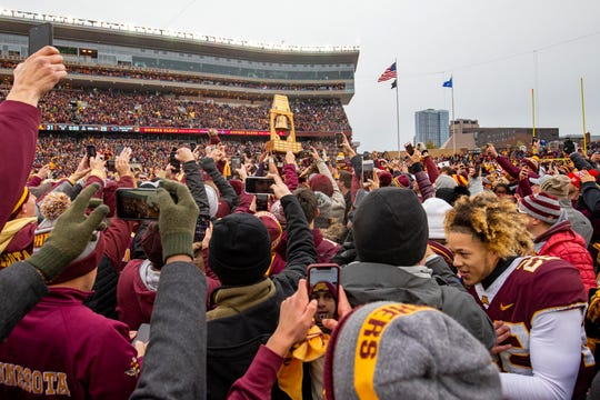 Minnesota players hold up the Governor Liberty Bell trophy after defeating the Penn State at TCF Bank Stadium.