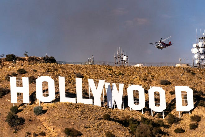 A firefighting helitanker flies above the Hollywood Sign as smoke of the Barham Fire rises from in the hills behind in Los Angeles, California.