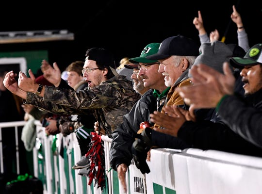 Hamlin fans clap and wave their team onward as the Pipers score a touchdown at the north end of Piper Stadium Friday.