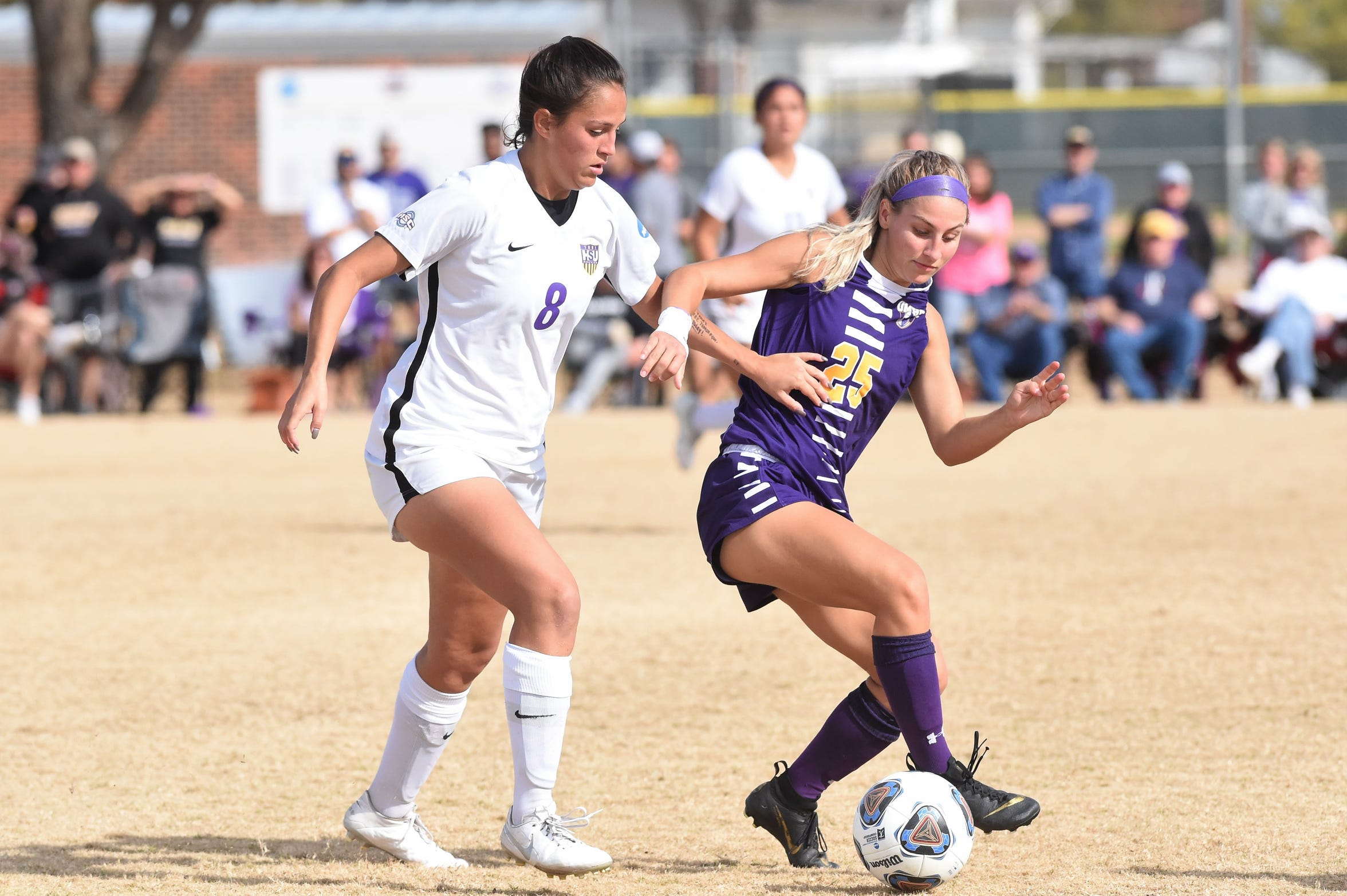 Hardin-Simmons' Taylor Bernal (8) holds off Mary Hardin-Baylor's Shay Smith (25) during the ASC tournament championship at the HSU Soccer Complex on Sunday, Nov. 10, 2019. The Cowgirls won 2-0 for their 17th-straight tournament title.