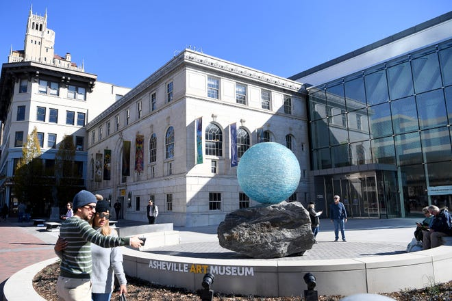 """A couple takes a selfie next to Henry RichardsonÕs """"Reflections on Unity""""Êin the front plaza of the Asheville Art Museum on Nov. 10, 2019."""