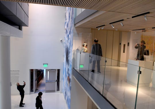 "A man leans back to try to photograph KenÊFandellÕs  more than 30-foot tall installation ""The Sky Above Here (Asheville, NC)"" in the Windgate Foundation Atrium of the newly remodeled Asheville Art Museum as others explore during a member preview on Nov. 10, 2019."