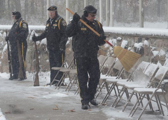 Brian Mohlman of the Fort Custer National Cemetery Honor Guard sweeps away some snow before the program.