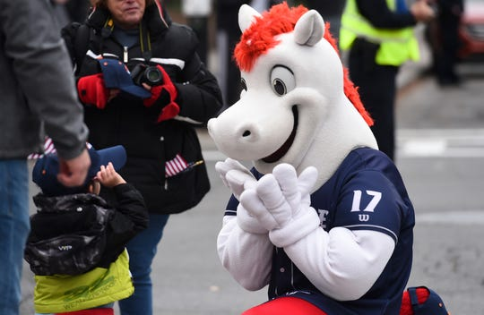 Rowdy, the Binghamton Rumble Ponies mascot, jokes with a child along the parade route of the annual Veterans Day Parade in downtown Binghamton on Monday, November 11, 2019.
