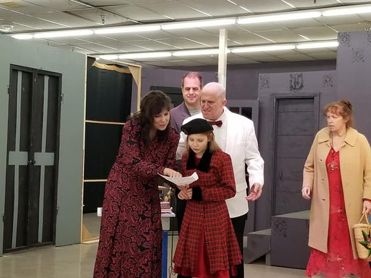 "Grace Farrell (Diane Daniels, left) and Oliver Warbucks (Jeffrey Bassett) have news that'll make Annie (Zoe Cook) say ""Leapin' Lizards!"" Drake (Marsh Marshall) and Miss Hannigan (Kim Myers, right) are interested spectators."