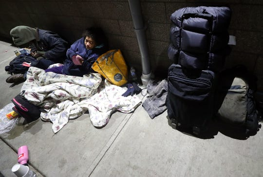 David Lund, left, and Katrina Sprague prepare to spend the night outside of the Salvation Army building on Thursday.