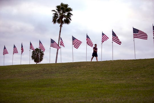 A man walks past flags installed along Ocean Drive on Monday, November 11, 2019. The annual Flags for Heroes by the Rotary Club of Corpus Christi includes 1,000 flags beginning at Ropes Park to Cole Park.
